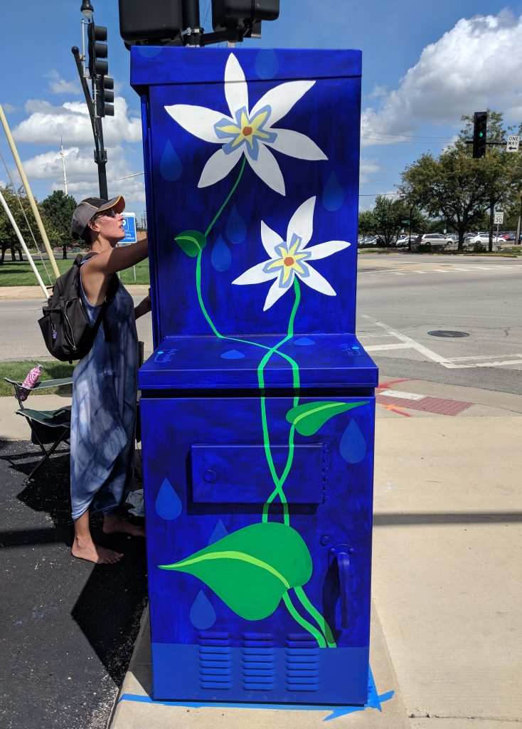 colorful and whimsical mural painter in Chicago area, Laura Lynne Art working on utility box flower mural