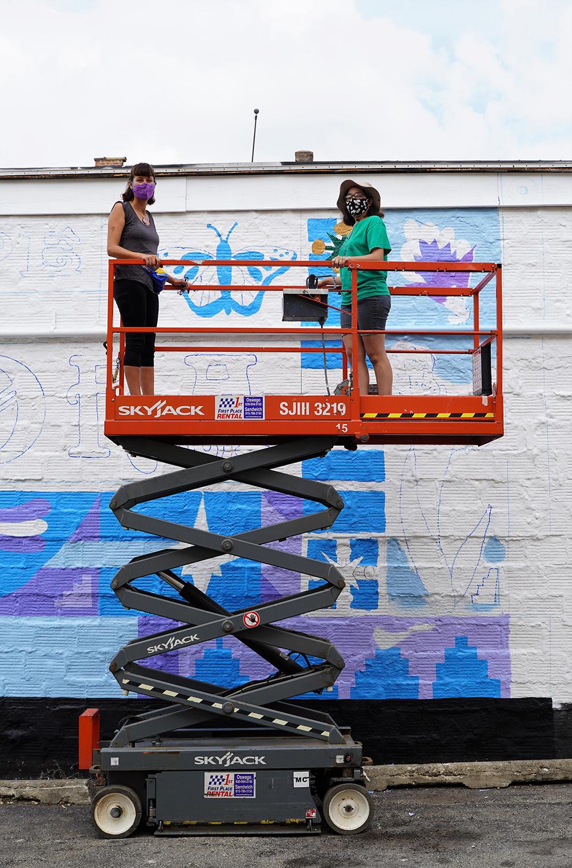 female mural artist team on scissor lift painting large scale mural